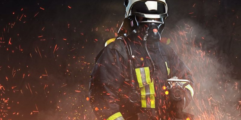 A firefighter dressed in a uniform in a studio.